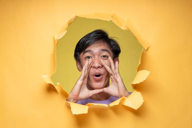 Gest krzyku, aby dać ducha pokazujący jego twarz przez dziurkę w papierze