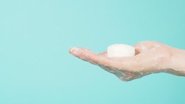 Gest mycia rąk mydłem i bańki na miętowym zielonym tle lub tiffany blue.