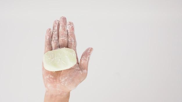 Gest mycia rąk z bańki mydła i pianki na białym tle.