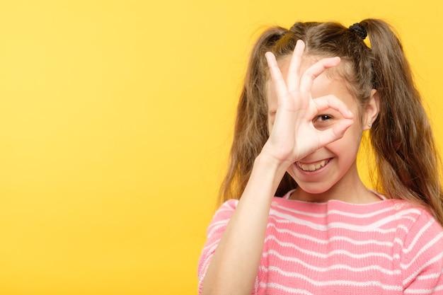 Gest ok. zabawna uśmiechnięta radosna dziewczyna patrząc przez palce.