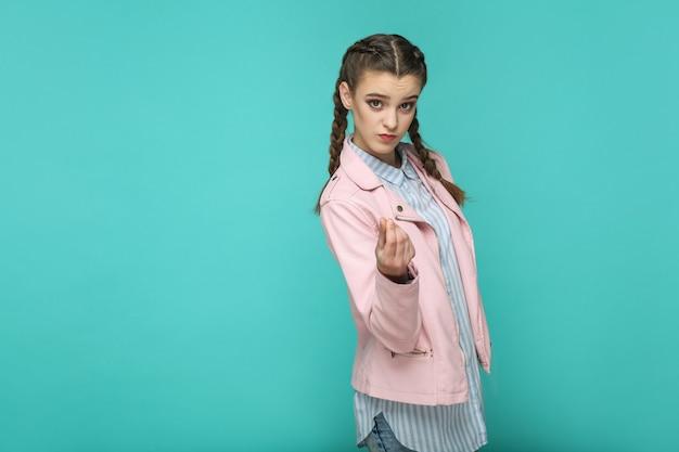 Gest pieniędzy. portret pięknej dziewczyny stojącej z makijażem i fryzurą brązowy warkocz w paski jasnoniebieską koszulę różową kurtkę. kryty, studio strzał na białym tle na niebieskim lub zielonym tle.