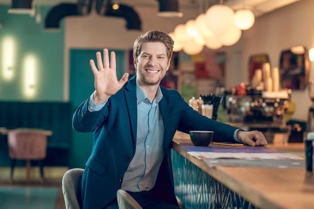 Gest, powitanie. uśmiechnięty atrakcyjny mężczyzna w garniturze, który podniósł rękę na powitanie, siedząc z kawą w kawiarni