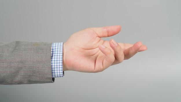 Gest pustej lewej ręki w szarym kolorze na szarym tle. biznesmen temat