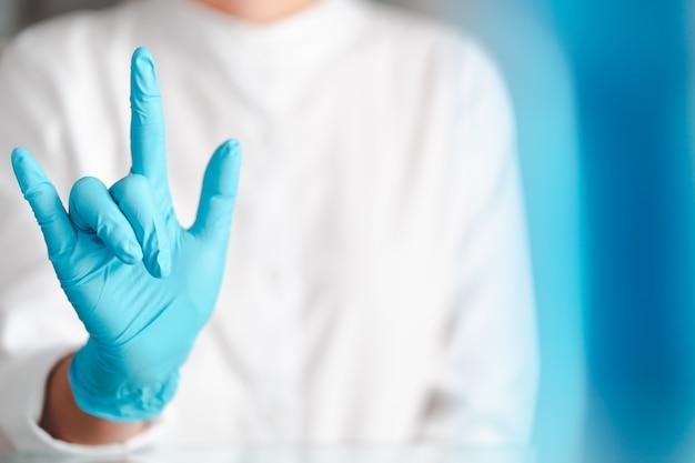 Gest rąk lekarza na sobie niebieskie rękawiczki, znak miłości
