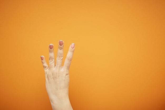 Gest, ręka pokazuje cztery palce na pomarańczowo.