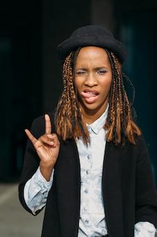 Gest rocka. nowoczesna młoda czarna dama. figlarny african american kobieta na ciemnym tle w selektywnej ostrości, stylowa kobieta, koncepcja radości