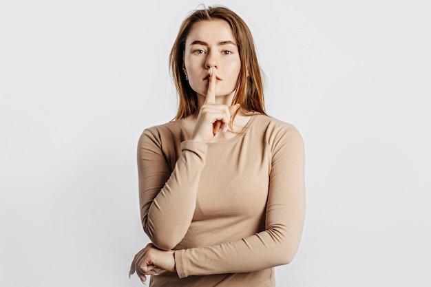 Gest shh. młoda piękna dziewczyna poważne trzymając palec na ustach na na białym tle