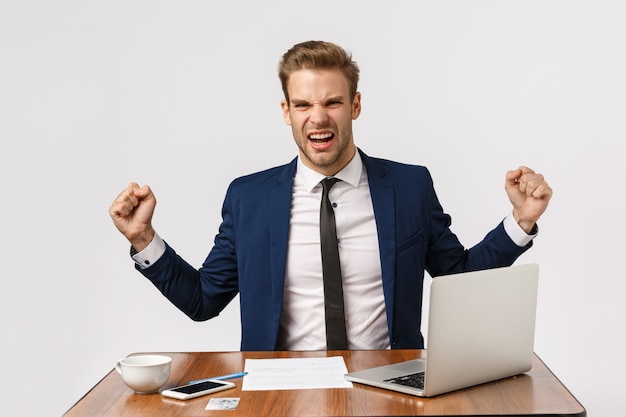 Gest sukcesu, zwycięstwa i uroczystości. rozochocony caucasian samiec model, biznesmen w klasycznym kostiumu, siedzący biurowy biurko z laptopem, dokumenty, wygrany zakład, pięści pompa rozochocona, biały tło