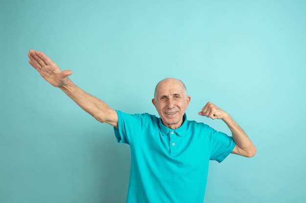 Gest zwycięzcy sukcesu. portret rasy kaukaskiej starszego m ?? czyzny na niebieskim tle studio. piękny męski model emocjonalny. pojęcie ludzkich emocji, wyrazu twarzy, sprzedaży, dobrego samopoczucia, reklamy. copyspace.