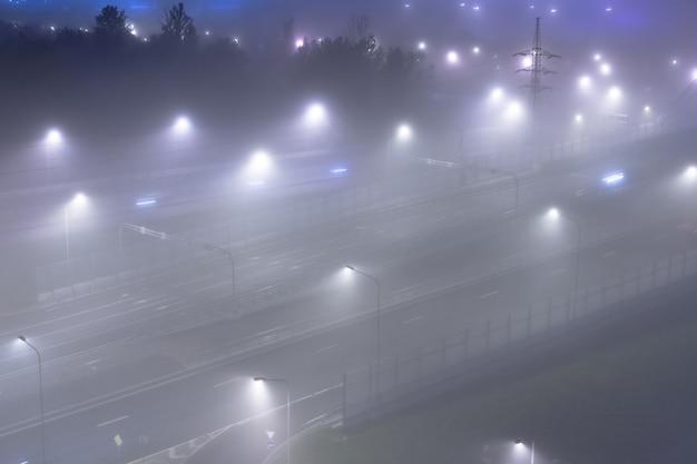 Gęsta mgła nad nocną autostradą w mieście. widok z góry.