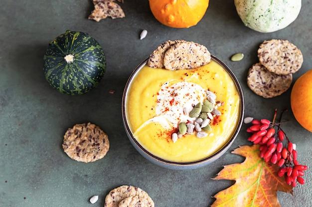 Gęsta wegetariańska zupa krem z pieczonej dyni z pestkami dyni, krakersami wieloziarnistymi i pestkami.