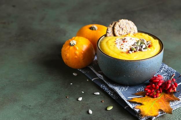 Gęsta zupa dyniowa ze śmietaną, krakersami wieloziarnistymi i pestkami w misce. zdrowe jedzenie wegetariańskie.