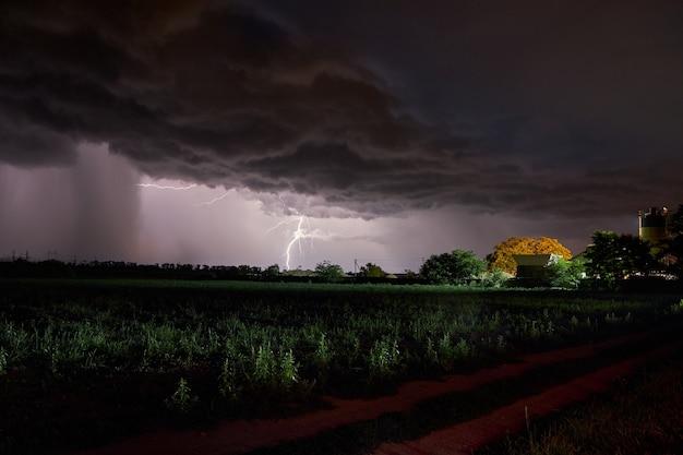 Gęste chmury nad wioską, deszcz i błyskawice w nocy