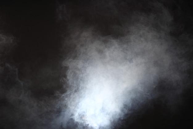 Gęste puszyste kłęby białego dymu i mgły na czarnym tle, abstrakcyjne chmury dymu, cały ruch niewyraźny, zamiar nieostry i wysoki kontrast niskiej ekspozycji, kopia miejsca na logo tekstowe