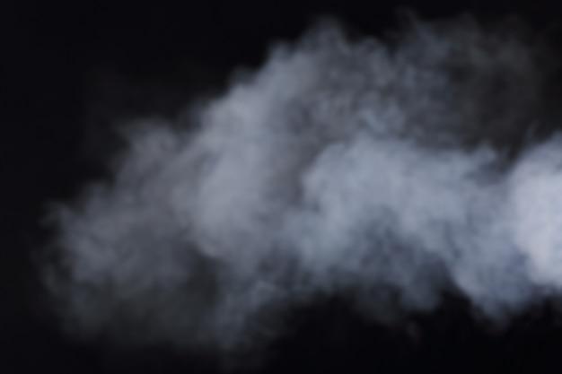 Gęste puszyste kłęby białego dymu i mgły na czarnym tle, abstrakcyjne chmury dymu, ruch niewyraźny