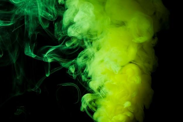 Gęste puszyste kłęby zielonego dymu na czarnym tle