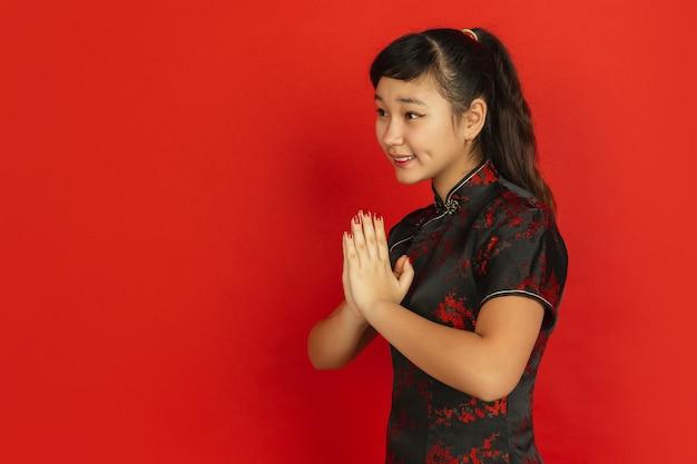 Gestem, dzięki z boku. szczęśliwego chińskiego nowego roku 2020. portret młodej dziewczyny azjatyckich na czerwonym tle. modelka w tradycyjne stroje wygląda na szczęśliwą. świętowanie, ludzkie emocje. copyspace.