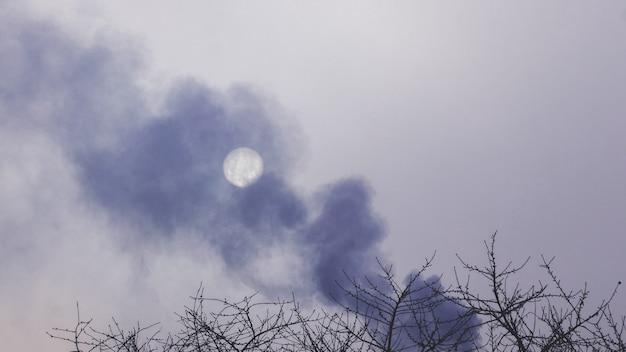 Gęsty dym na ciemnym niebie zasłania słońce, zanieczyszczając środowisko