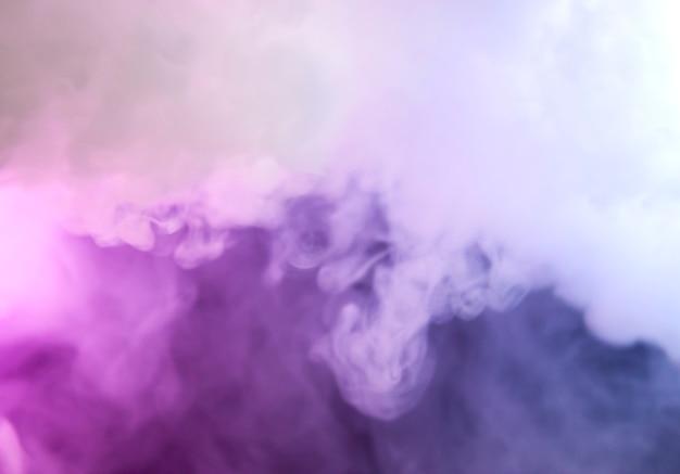 Gęsty dym w neonowym świetle. różowe i niebieskie światło, tekstura, tło. nieostre. streszczenie ciemne tło.