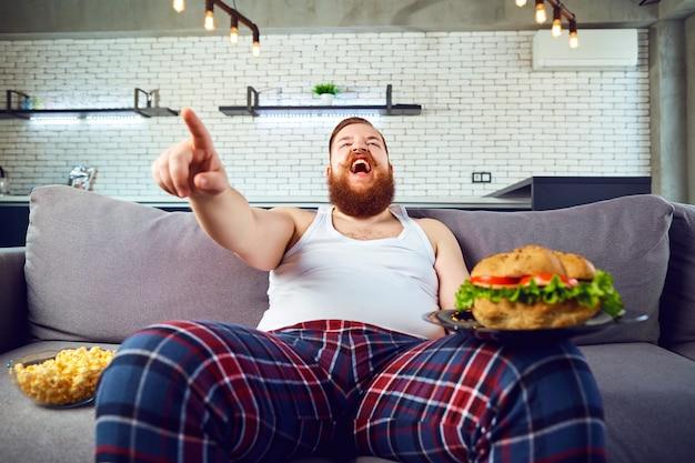 Gęsty śmieszny mężczyzna w piżamie z hamburgeriem siedzi na kanapie.