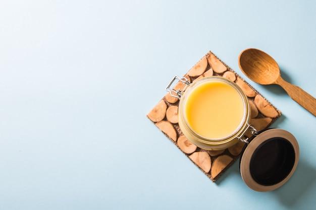 Ghee lub masło klarowane w słoiku i drewnianą łyżką na niebieskim tle. widok z góry. copyspace. masło ghee ma zdrowy tłuszcz i jest powszechnym składnikiem wielu indyjskich potraw