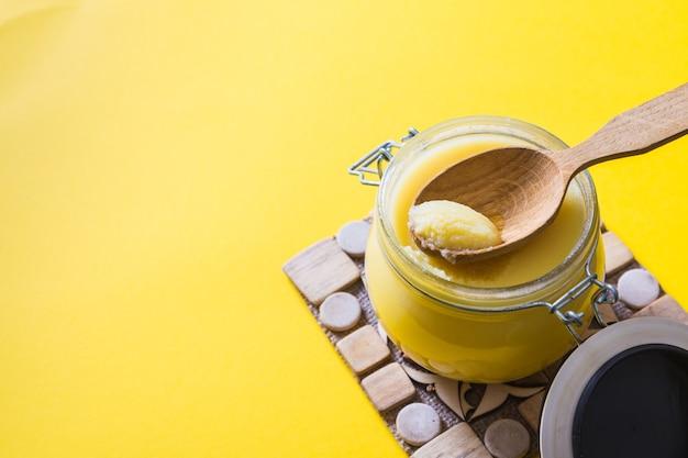 Ghee lub masło klarowane w słoiku i drewnianą łyżką na żółtym tle. widok z góry. copyspace. masło ghee ma zdrowy tłuszcz i jest powszechnym składnikiem wielu indyjskich potraw