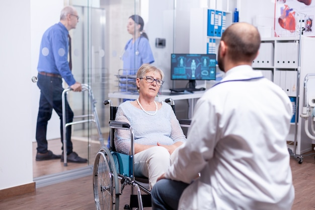 Giatra konsultujący inwalidę na wózku inwalidzkim w szpitalnej sali egzaminacyjnej