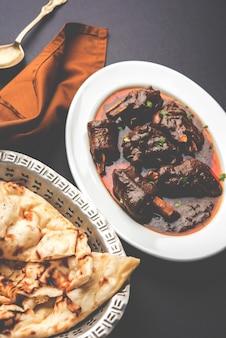 Gicz jagnięca lub baranina, znana również jako gosht paya lub curry khoor podawane z indyjskim roti pszennym, selektywne focus