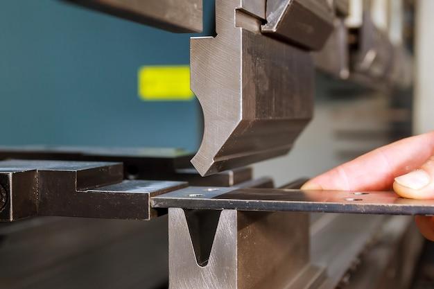 Gięcie blach na maszynie hydraulicznej w fabryce. zbliżenie.