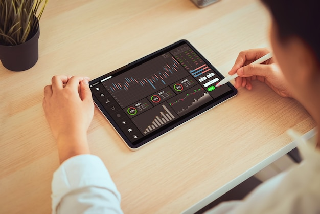 Giełdy koncepcja rynku, biznesmen przedsiębiorca patrząc na tablecie z wykresami analizy linii świec w pokoju biurowym, diagramy na ekranie.