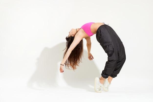 Giętka kobieta tancerka hip-hopu na białym tle z cieniem i copyspace, gdy wykonuje zgięcie do tyłu, jednocześnie balansując na palcach