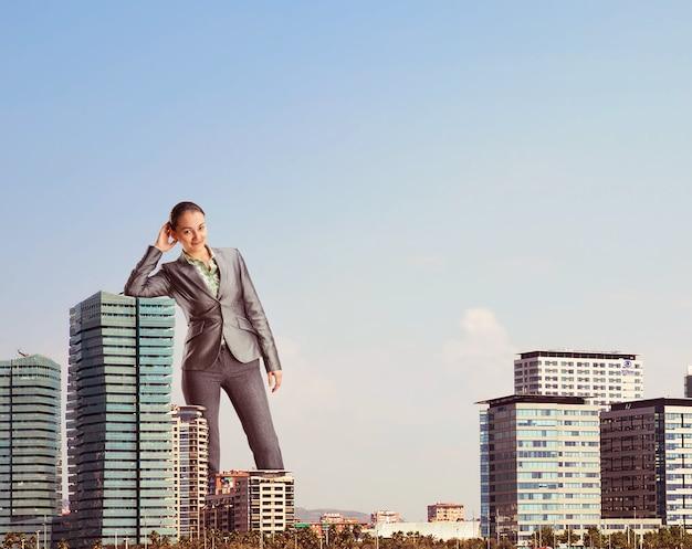 Gigantyczna bizneswoman wśród biurowych drapaczy chmur