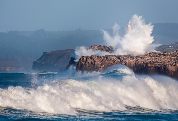 Gigantyczna fala przeskoczyła nad faro de mouro w santander. hiszpania