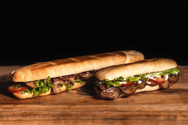 Gigantyczna kanapka z mięsem i mała kanapka na drewnianym stole z czarnym tłem.