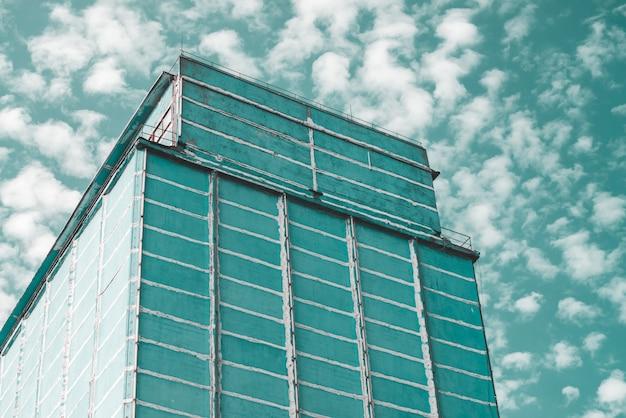 Gigantyczna ściana wielopiętrowego budynku produkcyjnego. malownicza stara odnowiona działająca fabryka. starzejący się obiekt przemysłowy. fasada dużego wieżowca produkcyjnego. zbliżenie obszaru przemysłowego. pochmurne niebo.