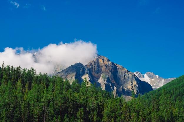 Gigantyczna skała w słonecznym dniu. skalisty grzbiet ze śniegiem za wzgórzami z lasami iglastymi. chmury na szczycie ogromnego śnieżnego pasma górskiego pod niebieskim niebem. klimatyczny krajobraz górski o majestatycznej naturze.