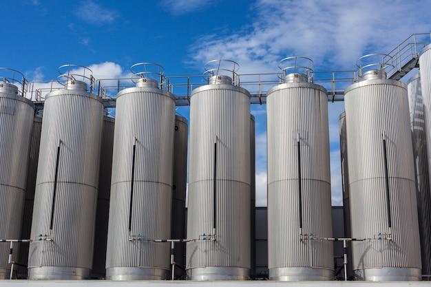 Gigantyczne zbiorniki przemysłowe na jasnym błękitnym niebie