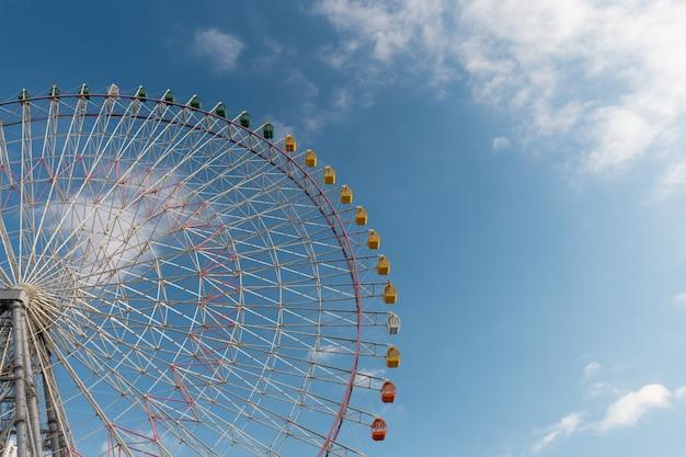 Gigantyczny ferris toczy wewnątrz niebieskie niebo, osaka, japonia