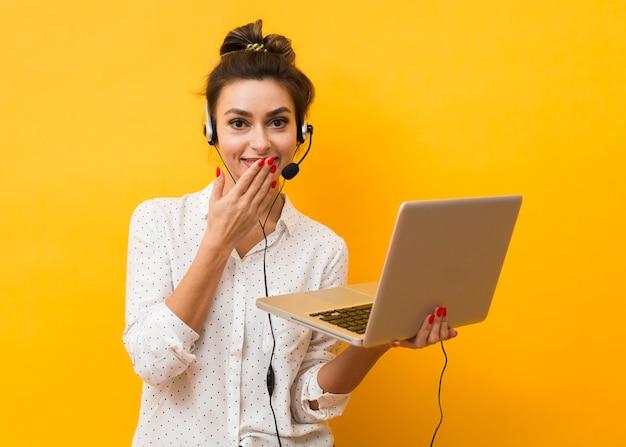 Giggly kobieta jest ubranym słuchawki i trzyma laptop