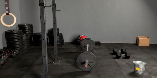 Gimnasio con barra y discos mas equipo de crossfit para hacer ejercicio