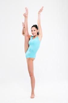 Gimnastyczka piękny elastyczny kobieta na białym tle na białej ścianie