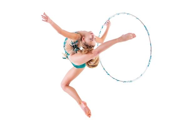 Gimnastyczka w szmaragdowym stroju kąpielowym wykonuje ćwiczenie z obręczą na białym