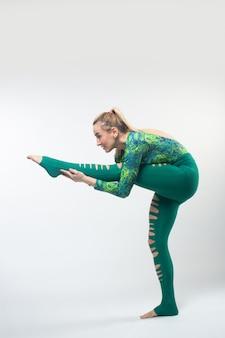 Gimnastyczka w wielokolorowych rajstopach podczas rozciągania