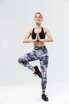 Gimnastyczna blond kobieta ubrana w odzież sportową, ćwicząca i medytująca z dłońmi na białym tle nad białą ścianą