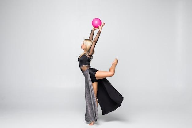 Gimnastyka profesjonalna sportowiec wykonuje z piłką na białym tle