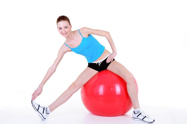 Gimnastyka z fitball młodej pięknej dziewczyny - na białym tle