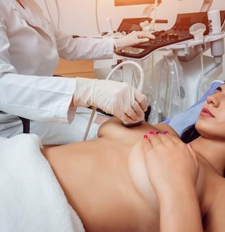 Ginekolog wykonujący badanie piersi u pacjenta za pomocą skanera ultrasonograficznego.