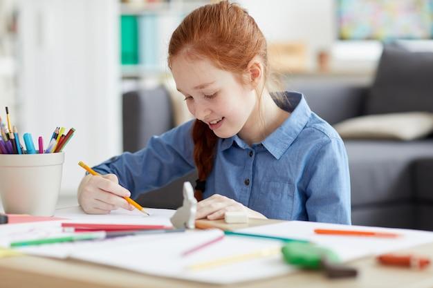 Ginger teenage girl drawing