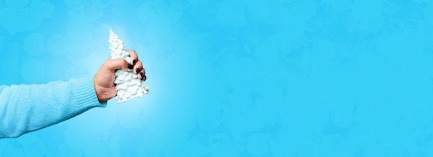 Gipsowa choinka w dłoni, na niebieskim tle, panoramiczny obraz makiety
