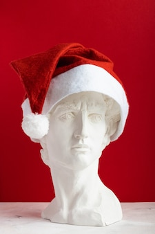 Gipsowa kopia rzeźby david michelangelo w czerwonym świątecznym kapeluszu świętego mikołaja na czerwonym tle